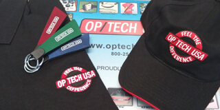 OP/TECH T-shirt, hat and keychains laid on a merchandise mat