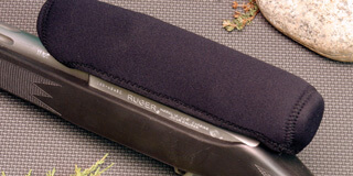 a rifle resting on a Work Mat with a Scope Skin cover